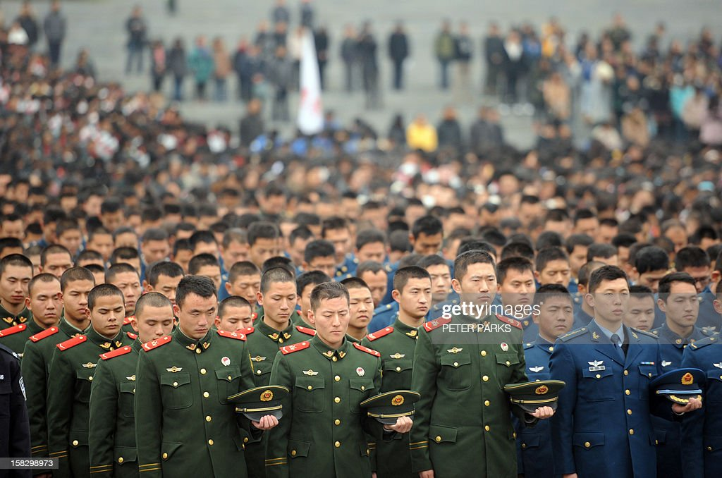Chinese military personnel attend a a ceremony for victims on the 75th anniversary of the Nanjing massacre at the Memorial Museum in Nanjing on December 13, 2012. Air raid sirens sounded in the Chinese city of Nanjing on December 13 as it marked the 75th anniversary of the mass killing and rape committed there by Japanese soldiers -- with the Asian powers' ties at a deep low. AFP PHOTO/Peter PARKS