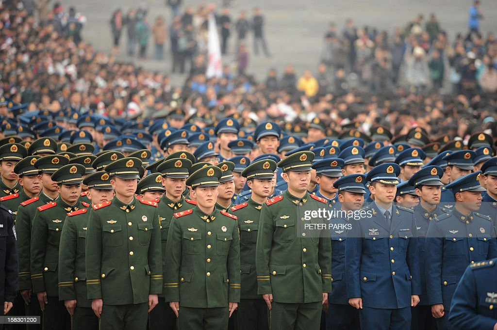 Chinese military personnel attend a ceremony for victims to mark the 75th anniversary of the Nanjing massacre at the Memorial Museum in Nanjing on December 13, 2012. Air raid sirens sounded in the Chinese city of Nanjing on December 13 as it marked the 75th anniversary of the mass killing and rape committed there by Japanese soldiers -- with the Asian powers' ties at a deep low. AFP PHOTO/Peter PARKS
