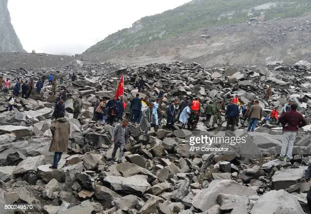 CORRECTION Chinese military police and rescue workers are seen at the site of a landslide in in Xinmo village Diexi town of Maoxian county Sichuan...
