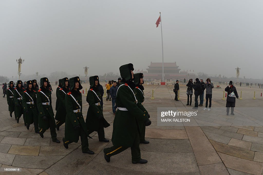 Chinese military policemen march through Tiananmen Square during heavy air pollution in Beijing on January 30, 2013. Beijing urged residents to stay indoors on January 30 as emergency measures were rolled out aimed at countering a heavy cloud of smog blanketing the Chinese capital and swathes of the country. AFP PHOTO/Mark RALSTON
