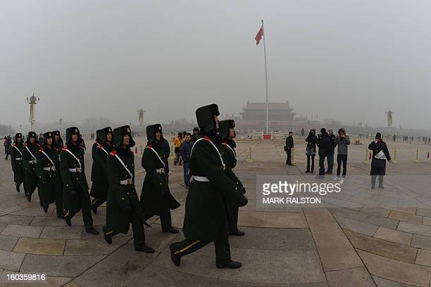 Chinese military policemen march through Tiananmen Square during heavy air pollution in Beijing on January 30 2013 Beijing urged residents to stay...