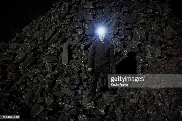 A Chinese mine worker wears a headlamp as he stands in a pile of coal at a mine on November 25 2015 in Shanxi China A history of heavy dependence on...
