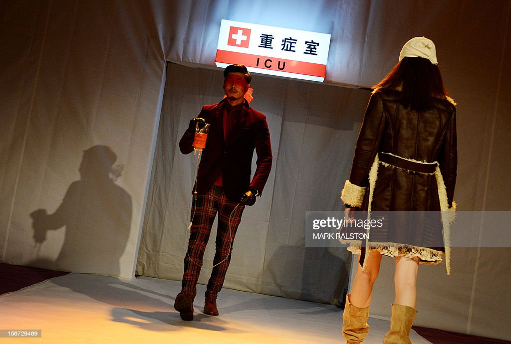 A Chinese model carries an IV bag during the 'Toxic Threads - The Big Fashion Stitch-up' fashion parade organized by Greenpeace to highlight chemical contamination in the fashion industry, in Beijing on November 20, 2012. According to Greenpeace, nearly two thirds of the clothing tested proved positive for hormone-disrupting chemicals and dyes that release cancer-causing substances. AFP PHOTO/Mark RALSTON