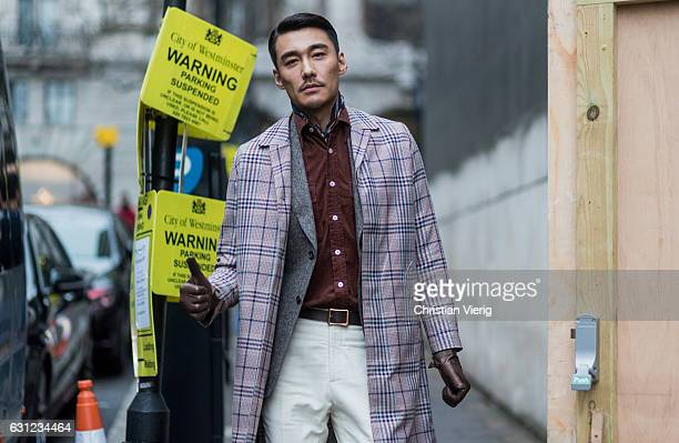 Chinese model Hu Bing wearing a plaid coat brown leather gloves during London Fashion Week Men's January 2017 collections at KTZ on January 8 2017 in...