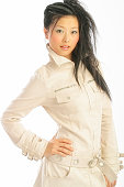 A chinese model poses in fashionable clothing in the studio.