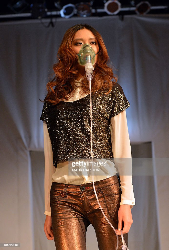 A Chinese model wears a face mask during a 'Toxic' fashion parade organized by Greenpeace to highlight chemical contamination in the fashion industry, in Beijing on November 20, 2012. Greenpeace released the results of a months-long global investigation into some of the world's top-selling fast fashion houses, with sample products purchased from nearly 30 countries. According to Greenpeace, nearly two thirds of the clothing tested positive for hormone-disrupting and dyes that release cancer-causing substances. AFP PHOTO/Mark RALSTON