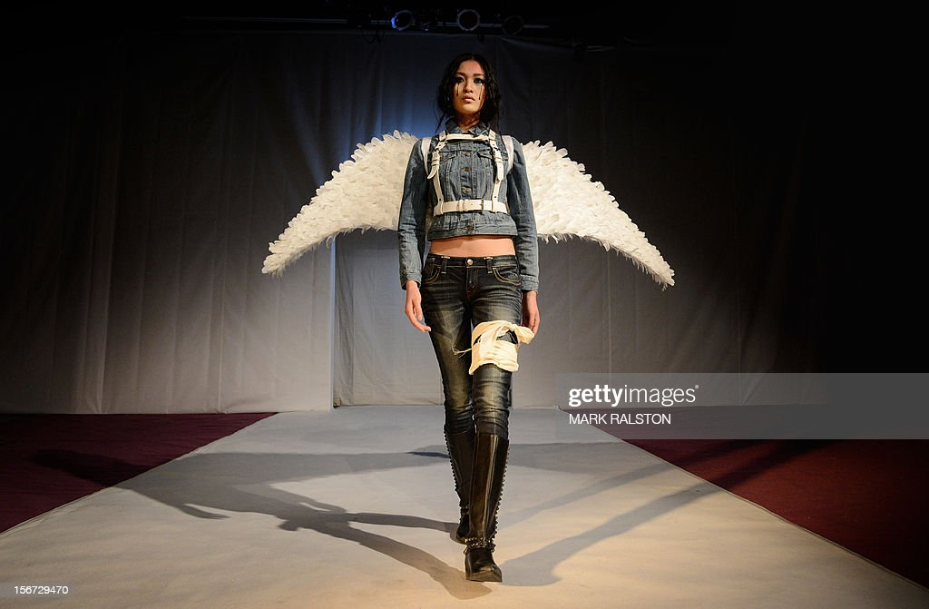 A Chinese model with angel wings and a bandaged leg walks during the 'Toxic Threads - The Big Fashion Stitch-up' fashion parade organized by Greenpeace to highlight chemical contamination in the fashion industry, in Beijing on November 20, 2012. According to Greenpeace, nearly two thirds of the clothing tested proved positive for hormone-disrupting chemicals and dyes that release cancer-causing substances. AFP PHOTO/Mark RALSTON