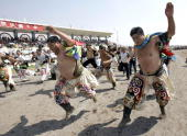 Chinese Mongolian wrestlers show off their moves during a parade to mark the start of the Naadam festival on the grassland of Gegental Steppe in...