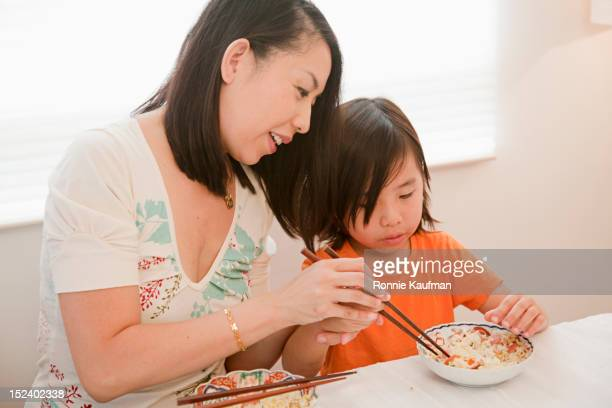 Chinese mother teaching son to use chopsticks