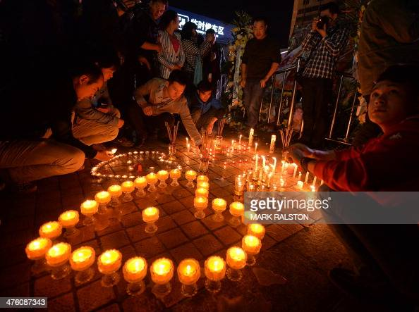 Chinese mourners light candles at the scene of the terror attack at the main train station in Kunming Yunnan Province on March 2 2014 Knifewielding...