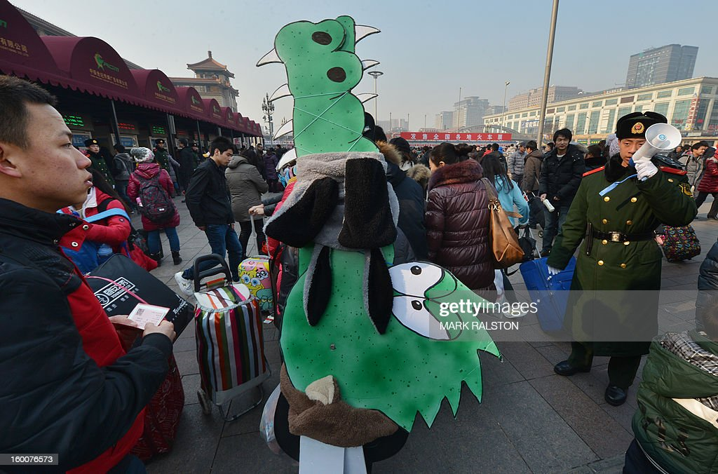 A Chinese musician (C) is watched by a military policeman (R) as she carries crocodile artwork back to her hometown in Inner Mongolia while she joins the annual Lunar New Year exodus at Beijing train station on January 26, 2013. The holiday also known as the Spring Festival sees tens of millions of migrant workers who provide the labour in the country's prosperous cities return to their villages and towns to spend time with the famillies left behind. AFP PHOTO/Mark RALSTON