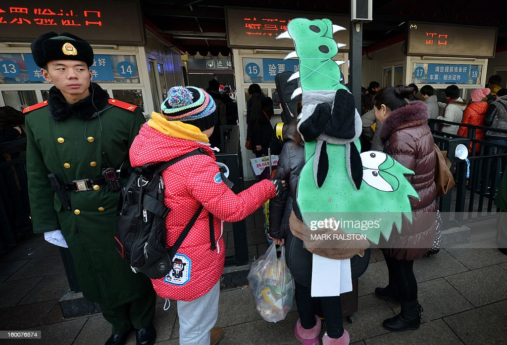 A Chinese musician (R) is watched by a military policeman (L) as she carries crocodile artwork back to her hometown in Inner Mongolia while she joins the annual Lunar New Year exodus at Beijing train station on January 26, 2013. The holiday also known as the Spring Festival sees tens of millions of migrant workers who provide the labour in the country's prosperous cities return to their villages and towns to spend time with the famillies left behind. AFP PHOTO/Mark RALSTON