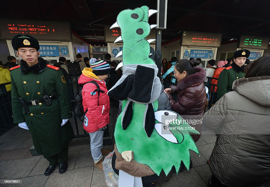 A Chinese musician (C) is watched by a military policeman (L) as she carries crocodile artwork back to her hometown in Inner Mongolia while she joins the annual Lunar New Year exodus at Beijing train station on January 26, 2013. The holiday also known as the Spring Festival sees tens of millions of migrant workers who provide the labour in the country's prosperous cities return to their villages and towns to spend time with the famillies left behind. AFP PHOTO/Mark RALSTON