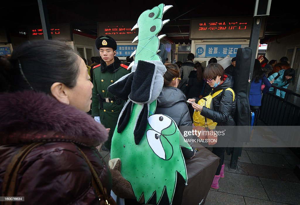 A Chinese musician (L) is watched by a military policeman (2nd L) as she carries crocodile artwork back to her hometown in Inner Mongolia while she joins the annual Lunar New Year exodus at Beijing train station on January 26, 2013. The holiday also known as the Spring Festival sees tens of millions of migrant workers who provide the labour in the country's prosperous cities return to their villages and towns to spend time with the famillies left behind. AFP PHOTO/Mark RALSTON