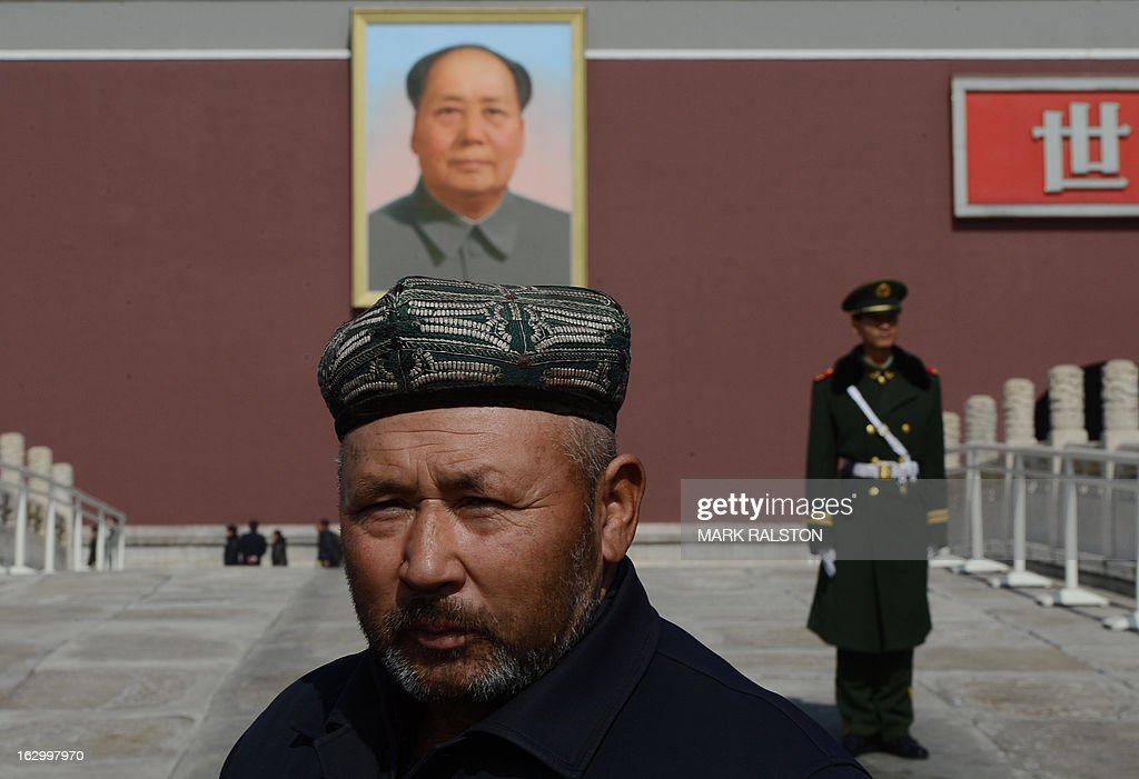 A Chinese muslim known as a 'Uighurs' from Xinjiang Province pose for photos in front of a portrait of Mao Zedong before the opening session of the Chinese People's Political Consultative Conference (CPPCC) at the Great Hall of the People in Beijing on March 3, 2013. Thousands of delegates from across China meet this week to seal a power transfer to new leaders whose first months running the Communist Party have pumped up expectations with a deluge of propaganda. AFP PHOTO/Mark RALSTON