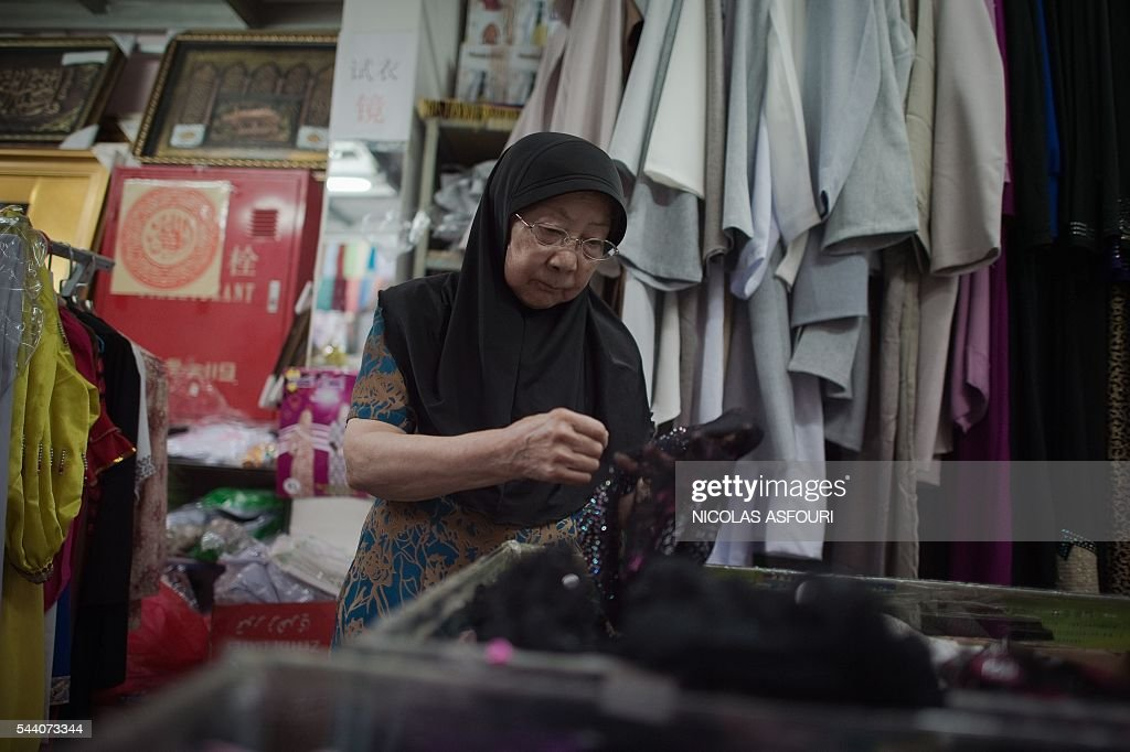 A Chinese Muslim looks for clothing in a shop during the Muslim fasting month of Ramadan in Beijing on July 1, 2016. Muslims fasting in the month of Ramadan must abstain from food, drink and sex from down to dusk, when they break the fast with a meal known as Iftar. / AFP / NICOLAS
