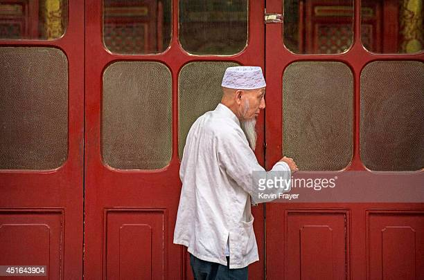 Chinese Muslim of the Hui ethnic minority closes the door of the prayer hall before breaking fast with others during the holy fasting month of...