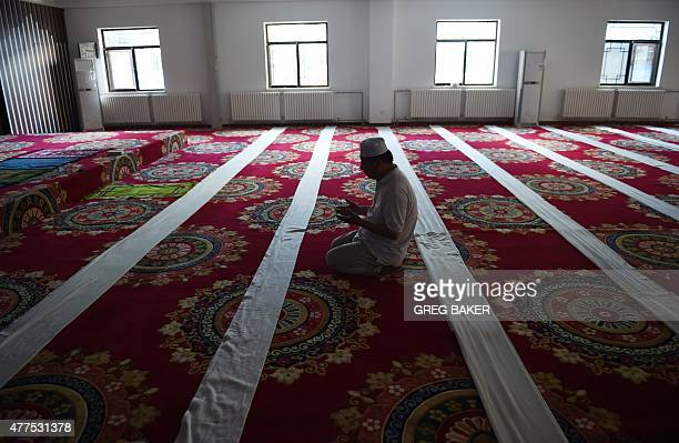 A Chinese Muslim offers prayers on the first day of Ramadan the Muslim holy month at a mosque in Beijing on June 18 2015 China has banned civil...