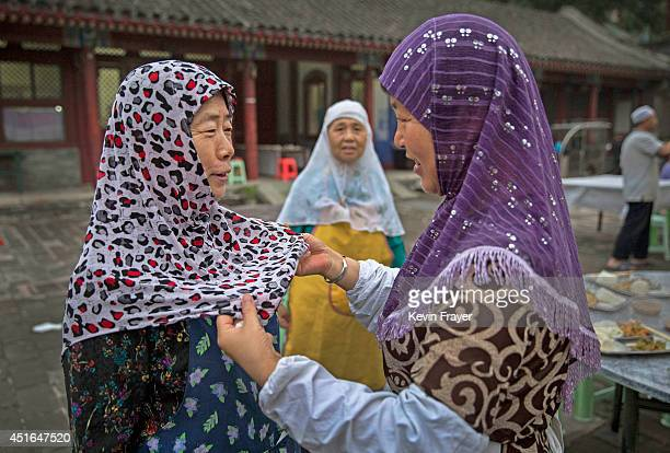 Chinese Muslim woman of the Hui ethnic minority has her headscarf adjusted as they prepare to break fast during the holy fasting month of Ramadan at...