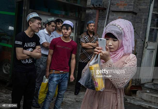Chinese Muslim woman of the Hui ethnic minority takes pictures before Eid Al Fitr prayers marking the end of the holy fasting month of Ramadan at the...