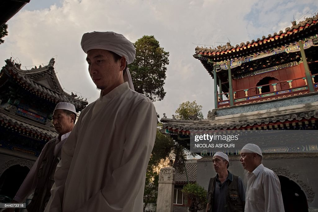Chinese Muslims enter to offer Friday prayers at the Niujie mosque during the Muslim fasting month of Ramadan in Beijing on July 1, 2016. Muslims fasting in the month of Ramadan must abstain from food, drink and sex from down to dusk, when they break the fast with a meal known as Iftar. / AFP / NICOLAS