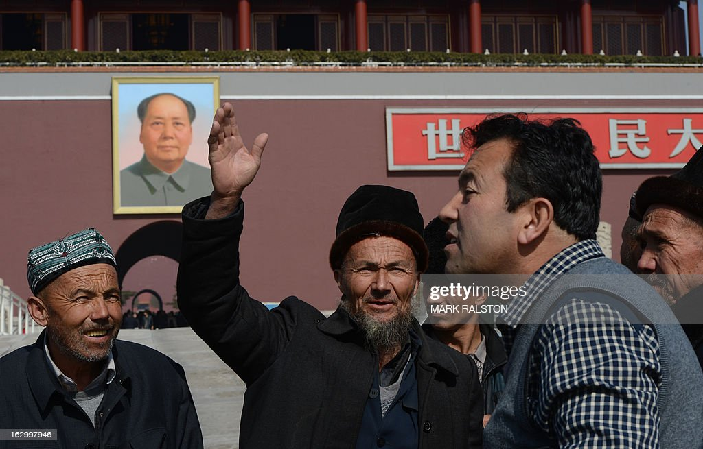 Chinese muslims known as 'Uighurs' from Xinjiang Province pose for photos in front of a portrait of Mao Zedong before the opening session of the Chinese People's Political Consultative Conference (CPPCC) at the Great Hall of the People in Beijing on March 3, 2013. Thousands of delegates from across China meet this week to seal a power transfer to new leaders whose first months running the Communist Party have pumped up expectations with a deluge of propaganda. AFP PHOTO/Mark RALSTON