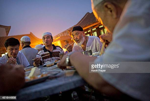 Chinese Muslims of the Hui ethnic minority eat as they break fast during the holy fasting month of Ramadan at the historic Niujie Mosque on July 3...