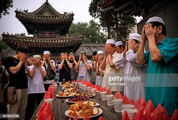 Chinese Muslims of the Hui ethnic minority pray over food before breaking fast during the holy fasting month of Ramadan at the historic Niujie Mosque...