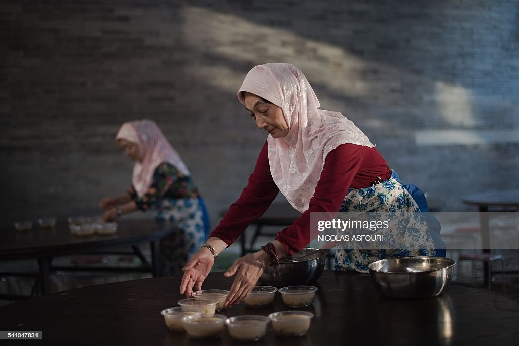 Chinese Muslims prepare a free meal to be served after Friday prayers at the Niujie mosque during the holy month of Ramadan in Beijing on July 1, 2016. Islam's holy month of Ramadan is celebrated by Muslims worldwide marked by fasting, abstaining from foods, sex and smoking from dawn to dusk for soul cleansing and strengthening the spiritual bond between them and the Almighty. / AFP / NICOLAS