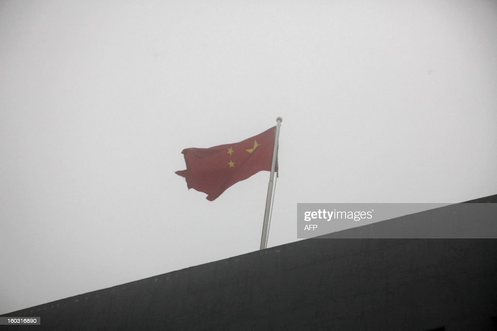 A Chinese national flag flag flies in heavy smog in Qingdao, east China's Shandong province on January 29, 2013. Residents across northern China battled through choking pollution on January 29, as air quality levels rose above index limits in Beijing amid warnings that the smog may not clear until January 31. CHINA OUT AFP PHOTO