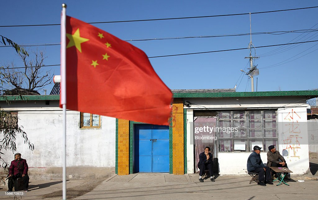 A Chinese national flag flies as people rest in front of a house in Pinggu, on the outskirts of Beijing, China, on Saturday, Nov. 17, 2012. China's gross domestic product slowed to 7.4 percent in the July-September period from a year earlier, the weakest in three years. Photographer: Tomohiro Ohsumi/Bloomberg via Getty Images