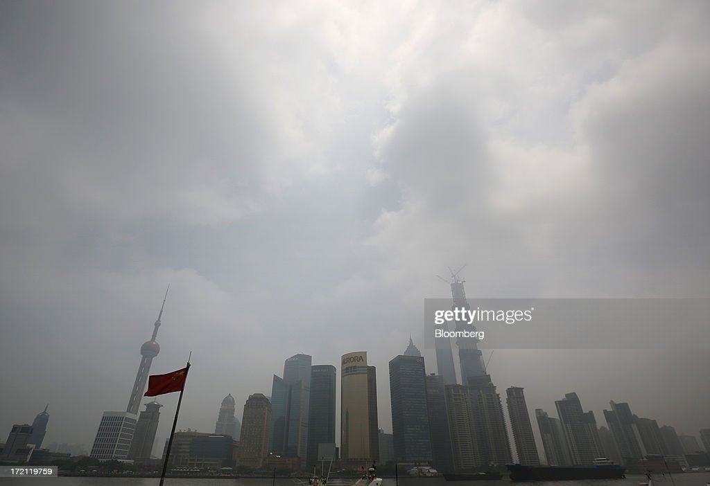 A Chinese national flag flies in front of buildings in the Lujiazui district of Shanghai, China, on Sunday, June 30, 2013. China's President Xi Jinping said officials shouldn't be judged solely on their record in boosting gross domestic product, the latest signal that policy makers are prepared to tolerate slower economic expansion. Photographer: Tomohiro Ohsumi/Bloomberg via Getty Images