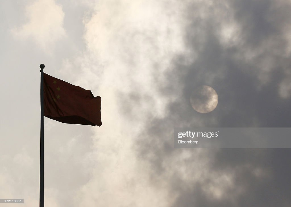 A Chinese national flag flies in front of the sun in Shanghai, China, on Sunday, June 30, 2013. China's President Xi Jinping said officials shouldn't be judged solely on their record in boosting gross domestic product, the latest signal that policy makers are prepared to tolerate slower economic expansion. Photographer: Tomohiro Ohsumi/Bloomberg via Getty Images