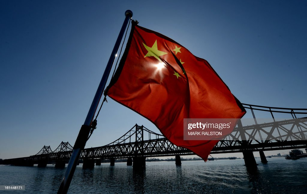 A Chinese national flag flies on a boat before the Sino-Korean Friendship bridge that spans the Yalu River linking the North Korean town of Sinuiju with the Chinese town of Dandong on February 11, 2013. A North Korean state media outlet has accused the United States of 'jumping to conclusions' that the North would soon stage a nuclear test, adding to the confusion over its immediate intentions. The US and its ally South Korea are 'fussing over speculation' without knowing exactly what action the North plans to take, Tongil Sinbo, a Japan-based pro-North weekly magazine funded by Pyongyang, said. AFP PHOTO/Mark RALSTON