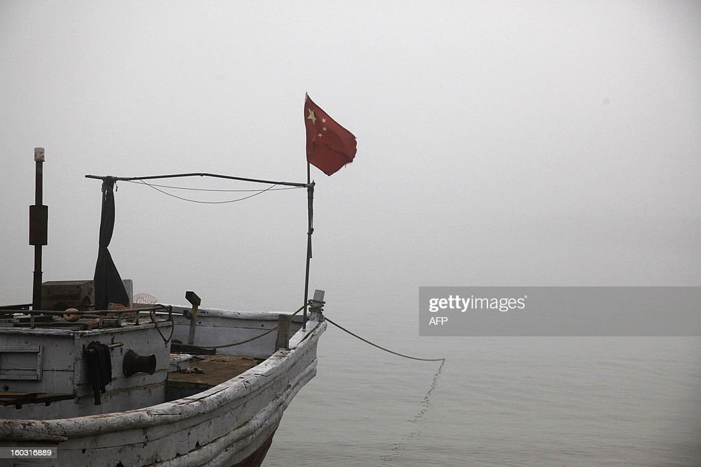 A Chinese national flag flies on a boat in heavy smog in Qingdao, east China's Shandong province on January 29, 2013. Residents across northern China battled through choking pollution on January 29, as air quality levels rose above index limits in Beijing amid warnings that the smog may not clear until January 31. CHINA OUT AFP PHOTO