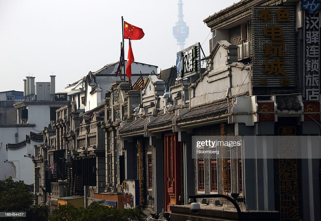 A Chinese national flag flies on a building in Wuhan, China, on Sunday, Oct. 20, 2013. China's economic expansion accelerated to 7.8 percent in the third quarter from a year earlier, the statistics bureau said Oct. 18, reversing a slowdown that put the government at risk of missing its 7.5 percent growth target for 2013. Photographer: Tomohiro Ohsumi/Bloomberg via Getty Images