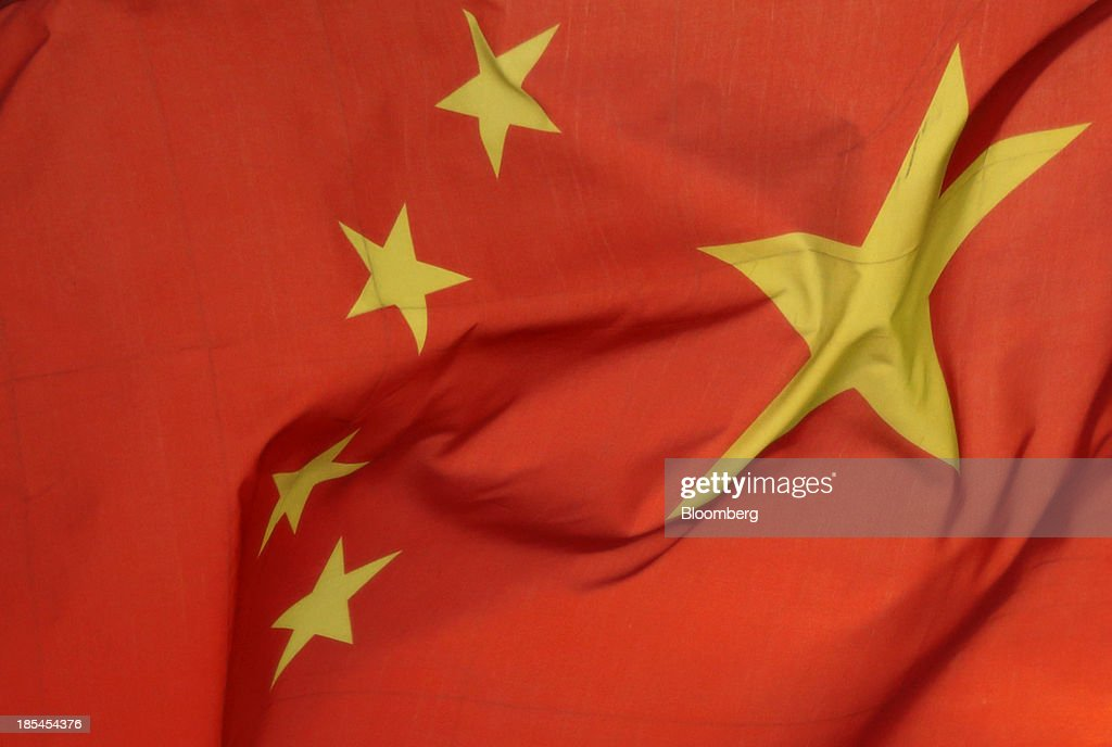 A Chinese national flag flies on a ferry as it crosses the Chang Jiang river in Wuhan, China, on Sunday, Oct. 20, 2013. China's economic expansion accelerated to 7.8 percent in the third quarter from a year earlier, the statistics bureau said Oct. 18, reversing a slowdown that put the government at risk of missing its 7.5 percent growth target for 2013. Photographer: Tomohiro Ohsumi/Bloomberg via Getty Images