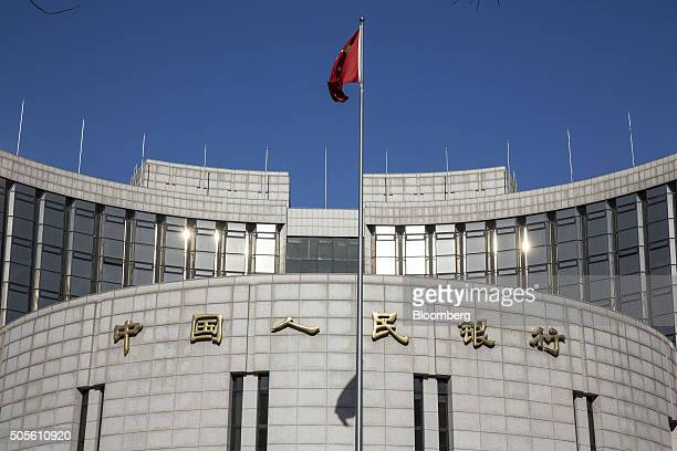 A Chinese national flag flies outside the People's Bank of China headquarters in Beijing China on Monday Jan 18 2016 China's economy slowed in...