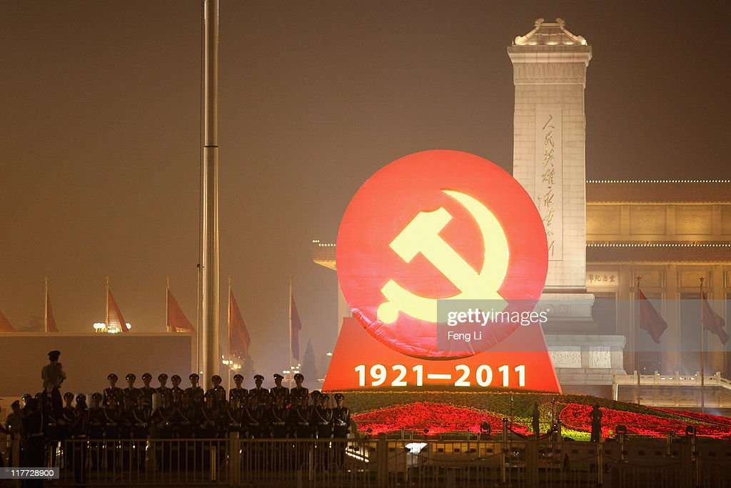 Chinese national flag guards take photo in front of an emblem of the Communist Party of China on the Tiananmen Square on June 30 2011 in Beijing...