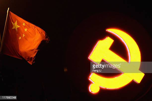 Chinese national flag waves near a giant communist emblem at Tiananmen Square on June 28 2011 in Beijing China This year's celebrations will mark the...