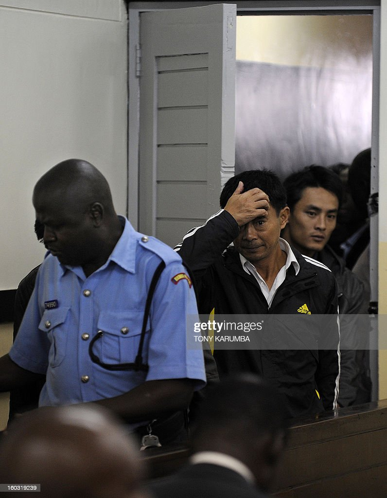 Chinese nationals, [from left] Liu Xuefeng [2-L] and, Gu Guisheng are led into a court on January 29, 2013 in Nairobi to answer to charges of smuggling illegal ivory. The four Chinese men who pleaded to smuggling thousands of dollars worth of ivory were handed fines of just $340 each. Four men were arrested on Sunday carrying ivory products including 40 chopsticks, six necklaces, bracelets and a pen holder, as well as two pieces of raw ivory weighing 9.6 kilogrammes; the raw ivory alone carrying an estimated black market value of value $24,000 in Asia. AFP PHOTO/Tony KARUMBA
