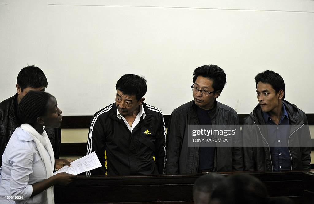 Chinese nationals, [from left] Liu Xuefeng [3-L], Gu Guisheng and Wang Chengbang and Qu Rongjun [obscured], appear in a courton January 29, 2013 in Nairobi to answer to charges of smuggling illegal ivory. The four Chinese men who pleaded guilty to smuggling thousands of dollars worth of ivory were handed fines of just $340 each. The four men were arrested on Sunday carrying ivory products including 40 chopsticks, six necklaces, bracelets and a pen holder, as well as two pieces of raw ivory weighing 9.6 kilogrammes; the raw ivory alone carrying an estimated black market value of value $24,000 in Asia. AFP PHOTO/Tony KARUMBA