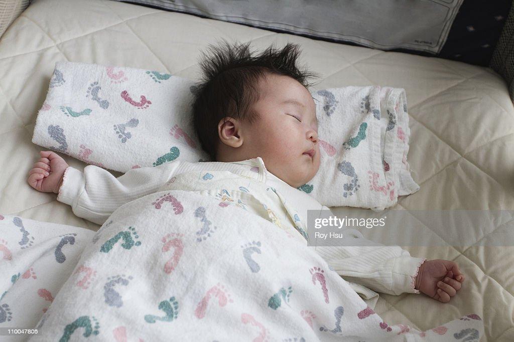 Chinese newborn baby girl sleeping in crib : Stock Photo