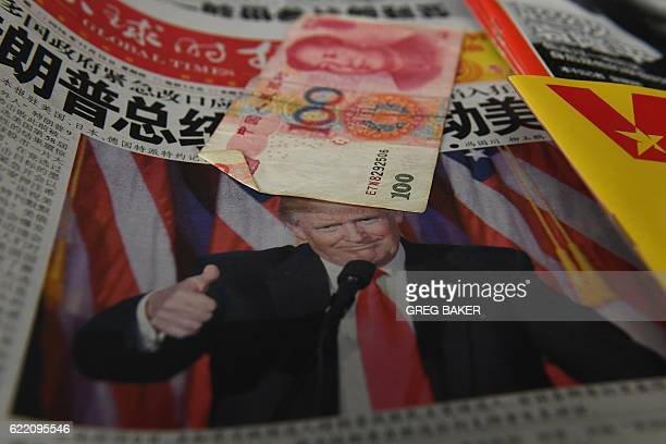 A Chinese newspaper featuring a photo of US Presidentelect Donald Trump that reads 'President Trump shakes America' is partially covered by a 100...