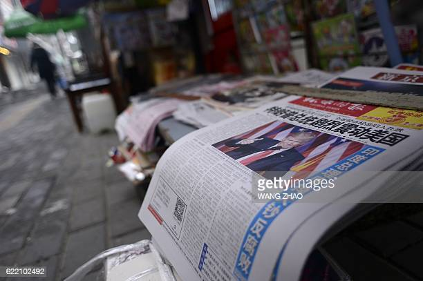 A Chinese newspaper featuring Donald Trump on the front page is displayed for sale in Beijing on November 10 2016 The US public on November 8 voted...