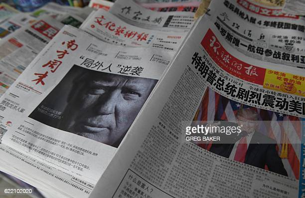 Chinese newspapers feature front page photos of US Presidentelect Donald Trump at a news stand in Beijing on November 10 2016 The US public on...