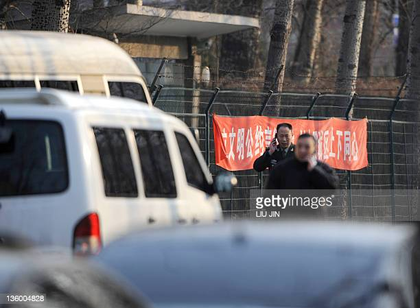 Chinese officials talk on mobile phones at the entrance of the North Korean embassy in Beijing on December 20 2011 China expressed shock at the death...