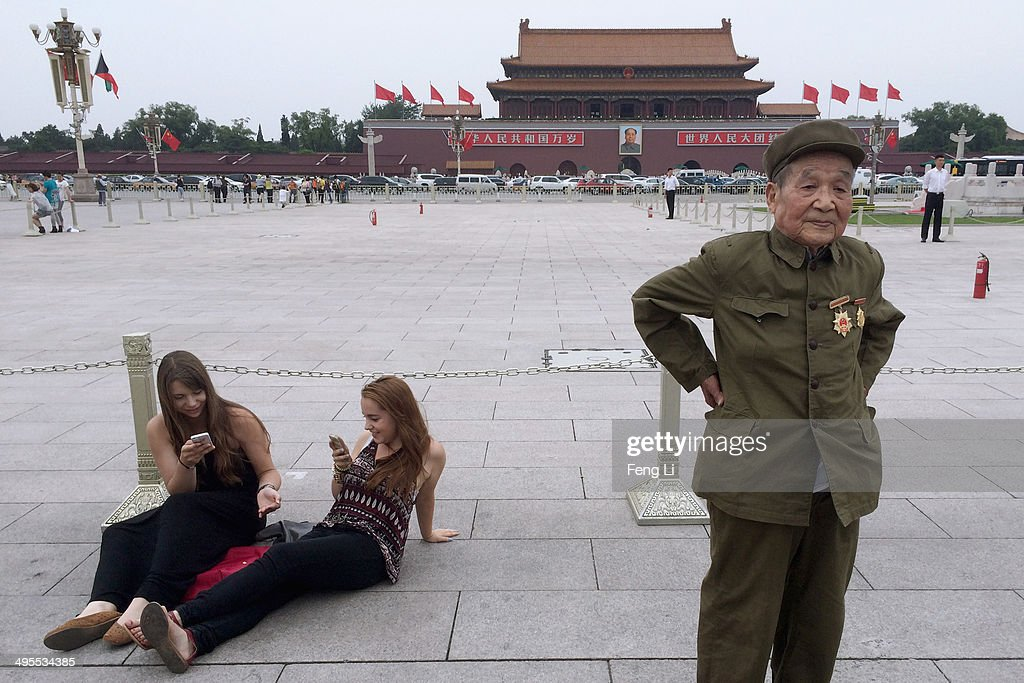 A Chinese old soldier wearing medals stands beside two foreign tourists in Tiananmen Square on June 4, 2014 in Beijing, China. Twenty-five years ago on June 4, 1989 Chinese troops cracked down on pro-democracy protesters and in the clashes that followed scores were killed and injured.