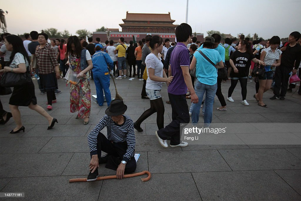 A Chinese oldman has a rest as tourists watching the customary ceremony of lowering flag at Tiananmen Square on May 3, 2012 in Beijing, China.