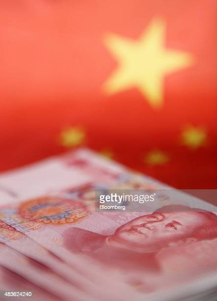 Chinese onehundred yuan banknotes are arranged for a photograph in Tokyo Japan on Tuesday Aug 11 2015 China devalued the yuan by the most in two...
